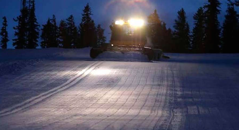 Ski piste and groomer showing prepaired snow